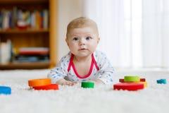 Neonata sveglia che gioca con il giocattolo di legno variopinto di crepitio Immagine Stock