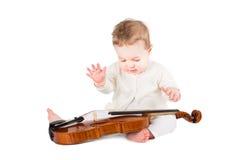 Neonata sveglia che gioca con un violino Immagini Stock