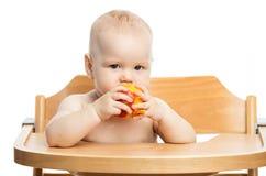 Neonata sveglia che mangia pesca mentre sedendosi nel seggiolone sopra bianco fotografia stock