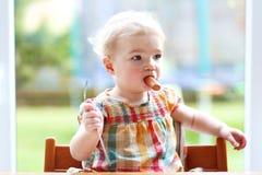Neonata sveglia che mangia salsiccia dalla forcella Fotografie Stock