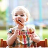 Neonata sveglia che mangia salsiccia dalla forcella Immagine Stock Libera da Diritti