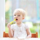 Neonata sveglia che mangia yogurt dal cucchiaio Fotografia Stock Libera da Diritti