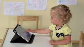 Neonata sveglia che per mezzo del computer della compressa che si siede vicino alla piccola tavola video d archivio