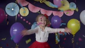 Neonata sveglia che prende i coriandoli luminosi e che celebra la sua festa di compleanno video d archivio