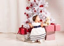 Neonata sveglia che si siede sotto l'albero di Natale Immagine Stock Libera da Diritti