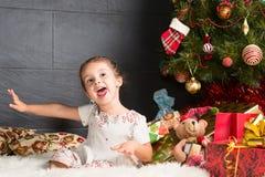 Neonata sveglia che si siede sulla coperta nel Natale interno Immagine Stock