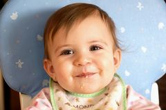 Neonata sveglia sorridente che mangia cereale Fotografia Stock Libera da Diritti