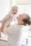 Neonata sveglia sorridente preoccupantesi della tenuta della madre Immagini Stock Libere da Diritti