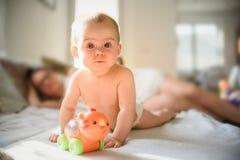 Neonata sveglia sulla pancia sullo strato in pannolino con un giocattolo sul sofà immagini stock libere da diritti