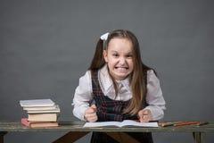 Neonata in un uniforme scolastico che si siede ad una tavola con i libri Immagini Stock Libere da Diritti