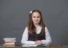 Neonata in un uniforme scolastico che si siede ad una tavola con i libri Fotografie Stock Libere da Diritti