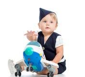 Neonata vestita come stewardess con il giocattolo dell'aeroplano Immagini Stock