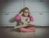 Neonata in vetri con un libro che si siede sul pavimento Immagine Stock