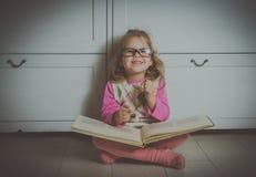 Neonata in vetri con un libro che si siede sul pavimento Immagini Stock Libere da Diritti