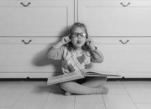 Neonata in vetri con un libro che si siede sul pavimento, in bianco e nero immagine stock libera da diritti