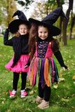 Neonate sveglie in costumi di carnevale e grandi cappelli neri della strega durante le celebrazioni di Halloween nel parco fotografia stock