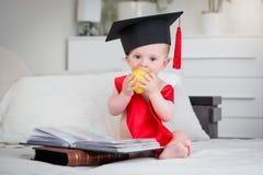 Neonato adorabile in cappuccio di graduazione che si siede sul letto con i libri e la mela mordace Immagine Stock Libera da Diritti