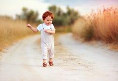 Neonato adorabile del bambino della testarossa nel funzionamento della tuta lungo la strada rurale di estate nel campo bruciato immagine stock
