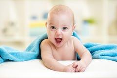 Neonato allegro che guarda fuori sotto un asciugamano blu Fotografia Stock Libera da Diritti