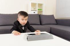Neonato asiatico che guarda sulla compressa immagine stock libera da diritti