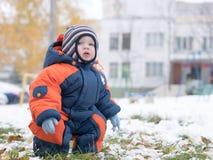Neonato attraente che gioca con la prima neve Sorride e guarda il pupazzo di neve A strisce luminoso della tuta blu-arancio spess Immagini Stock Libere da Diritti