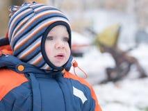 Neonato attraente che gioca con la prima neve Sorride e guarda il pupazzo di neve A strisce luminoso della tuta blu-arancio spess Immagine Stock Libera da Diritti