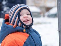 Neonato attraente che gioca con la prima neve Sorride e guarda il pupazzo di neve A strisce luminoso della tuta blu-arancio spess Fotografie Stock Libere da Diritti
