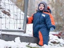 Neonato attraente che gioca con la prima neve Sorride e guarda il pupazzo di neve A strisce luminoso della tuta blu-arancio spess Fotografia Stock
