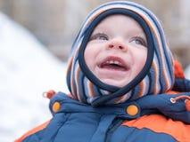 Neonato attraente che gioca con la prima neve Sorride e guarda il pupazzo di neve A strisce luminoso della tuta blu-arancio spess Fotografie Stock