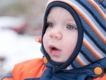 Neonato attraente che gioca con la prima neve Sorride e guarda il pupazzo di neve A strisce luminoso della tuta blu-arancio spess Immagini Stock