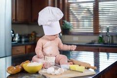 Neonato in cappello del cuoco unico coperto di farina che si siede sul tavolo da cucina Fotografie Stock Libere da Diritti
