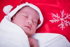 Neonato che dorme sul het di Santa e sul fondo rosso, fotografia stock