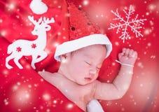 Neonato che dorme sul het di Santa e sul fondo rosso, immagine stock libera da diritti