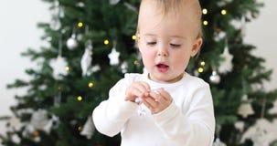 Neonato che esamina i giocattoli sull'albero di Natale archivi video