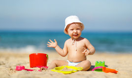 Neonato che gioca con i giocattoli e la sabbia sulla spiaggia Immagine Stock