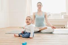 Neonato che gioca con i giocattoli mentre suo meditare della madre Immagini Stock Libere da Diritti