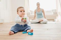 Neonato che gioca con i giocattoli mentre suo meditare della madre Fotografie Stock