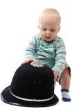 Neonato che gioca con il casco della polizia Immagine Stock