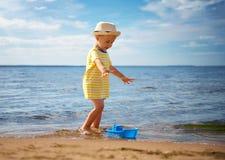 Neonato che gioca con il giocattolo della nave in mare Fotografie Stock