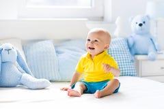 Neonato che gioca sul letto in scuola materna soleggiata Fotografia Stock Libera da Diritti