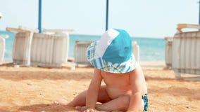 Neonato che gioca sulla spiaggia sabbiosa di estate vicino al mare Vacanza di estate alla spiaggia Estate, viaggio, festa archivi video