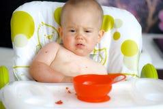 Neonato che mangia nel seggiolone con il fronte sudicio fotografia stock