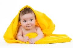 Neonato che si riposa e che sorride in un asciugamano giallo Fotografie Stock