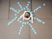 Neonato che si siede nei pezzi medi di puzzle piegati come forma del sole sul salone del sofà a casa Fotografia Stock