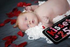 Neonato con i baci del rossetto da ogni parte di lui Fotografie Stock Libere da Diritti