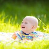 Neonato con la mela sul picnic del giardino della famiglia fotografia stock