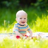 Neonato con la mela sul picnic del giardino della famiglia immagine stock libera da diritti
