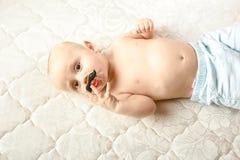 Neonato con la tettarella divertente con i baffi e le labbra Neonato in cappuccio tricottato immagini stock libere da diritti