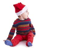 Neonato con un cappuccio di Santa che sembra stupito alla destra Fotografie Stock Libere da Diritti