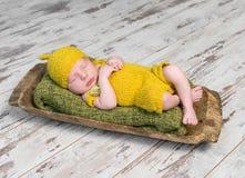Neonato in costume giallo che dorme sulla culla di legno Fotografia Stock